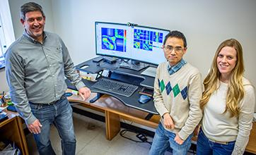 Research team stands by picture of hyperspectral data.