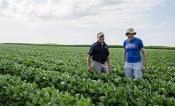 Steve Long and Don Ort stand in a soybean field.
